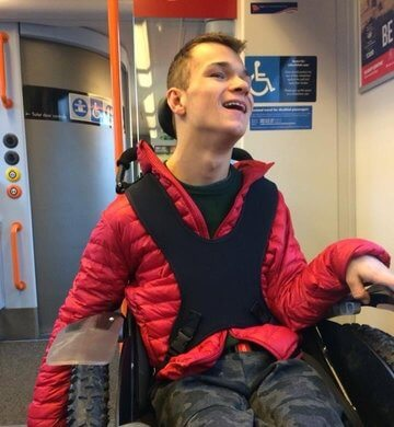 Young person in wheelchair on train