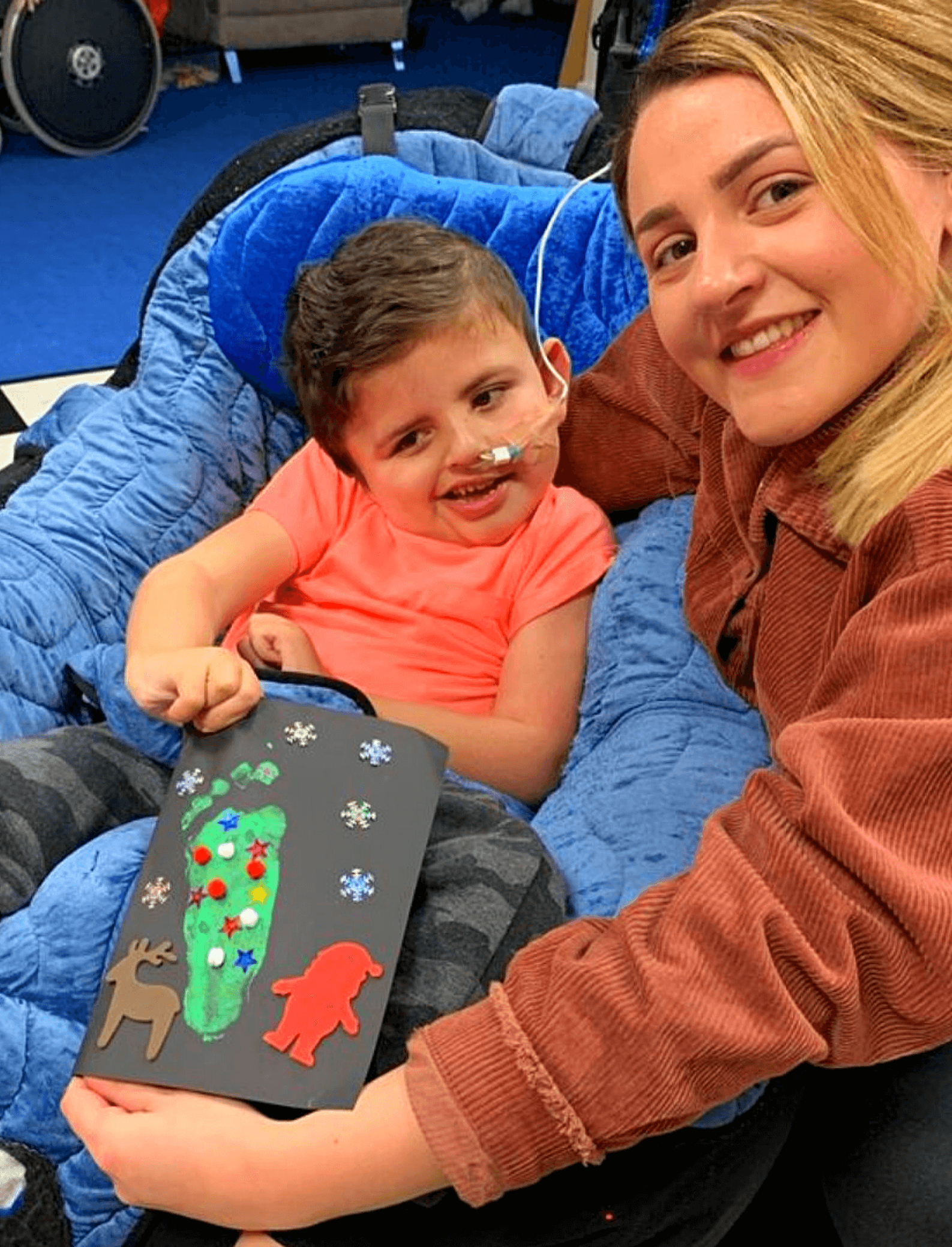 Young person and his support worker with his Christmas tree footprint picture